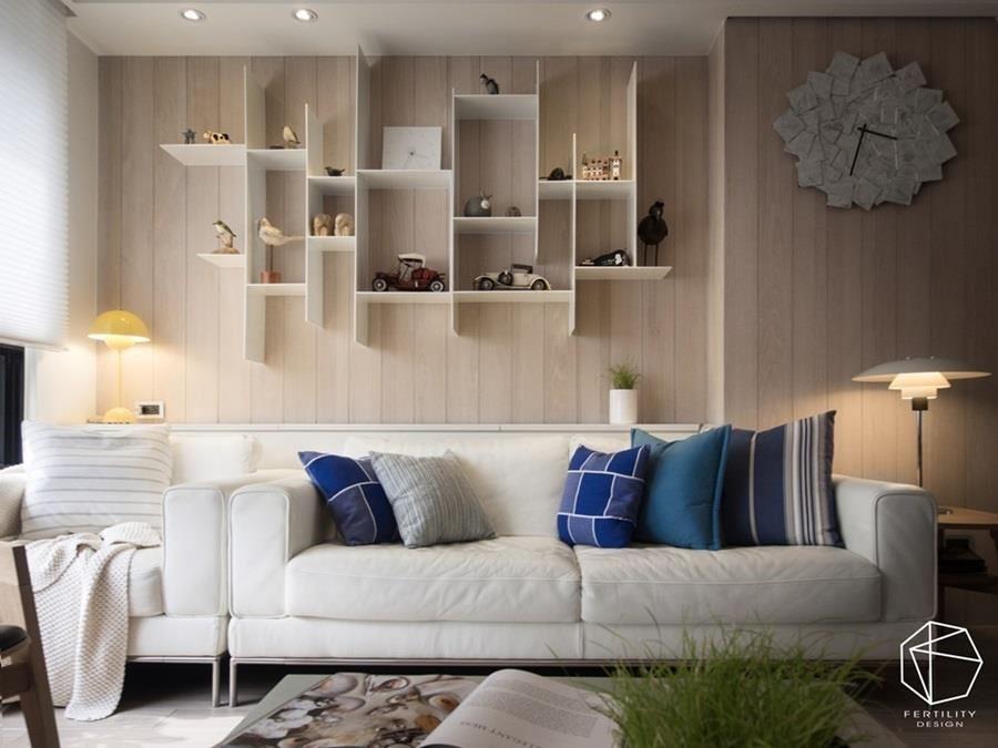 沙发背墙更以白色及木色做搭配,规划整座白色铁件展示架,透过利落的线条、呈现轻量化的美感,并摆设生活摆饰,随时展示美好回忆。
