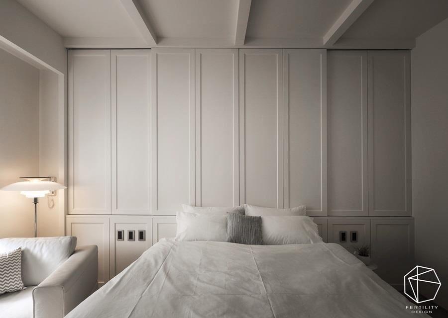 床头正位于梁下,因此设计师规划出有高低差的斜屋顶,并在背墙设置一整片的收纳柜,既有线条装饰感又极具功能性。