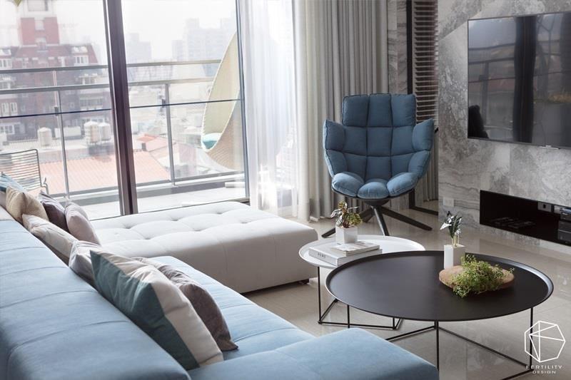 客厅陈列 L 型沙发、单椅等家具,透过各种深浅不一的蓝色调交织,营造美好层次。