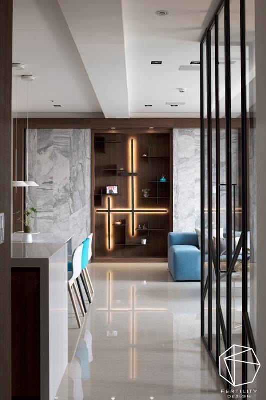 客厅背墙亦是走道端景,设计师特意在两面纹理丰厚的大理石墙面中,留出一面开放性展示柜,内嵌十字架造形灯,由着地面反射出的光束,活化了整体氛围的流动,成为一大视觉焦点。