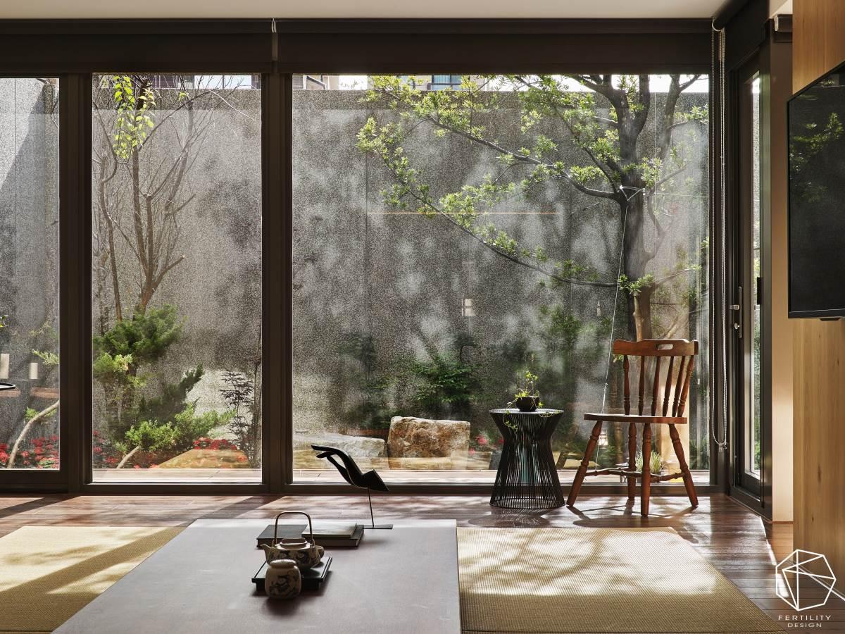 落地窗外布满美好绿栽,伴随着日光变化,筛落成千变万化的树影姿态,构成室内最天然的妆点元素,并摆置桌几与单椅,形塑充满日式风情的檐廊,可静待四季、坐看云起,尽情饱览庭院风景。