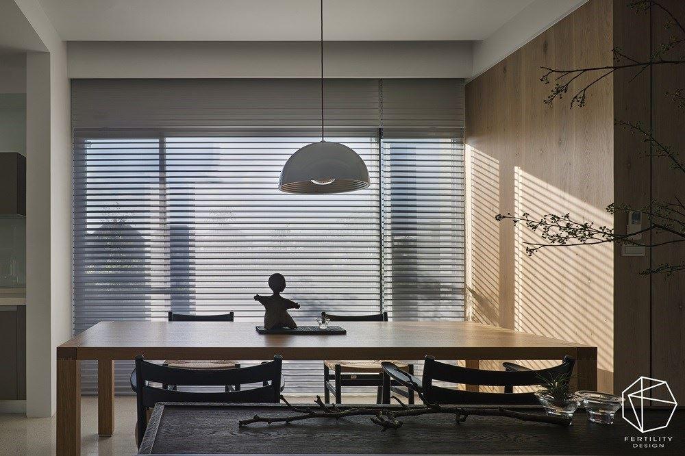 楼梯旁侧的闲置空间作为餐厨场域,采以开放式规划,藉由窗景迎接露台的绿意美景,同时安装卷帘引导光线,任光影筛落木皮墙面,围塑自然休闲的氛围。