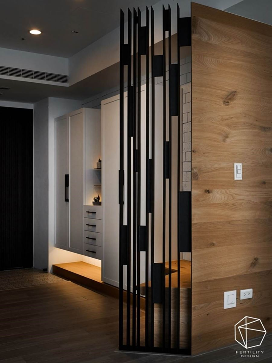 为了风水考虑,避免进门即见窗,在玄关与客厅间装设铁制格栅的木板,不仅解决风水问题,也替空间带来独特的层次感。