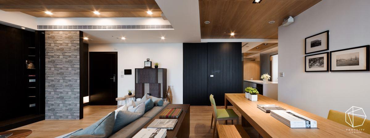 天花板则大量铺设橡木木皮,缔造温润质感,并以降版框设客厅上方的木梁设计,达到遮梁的目的。