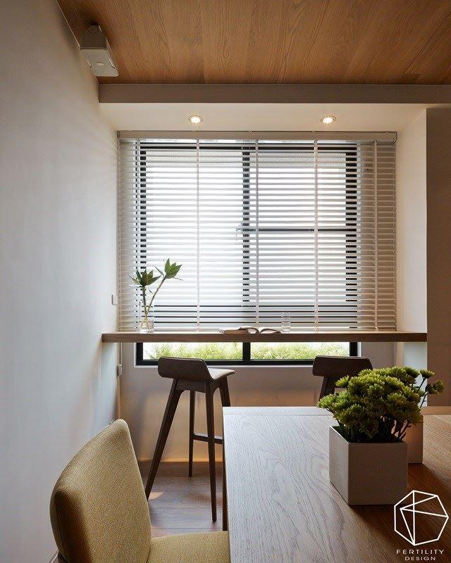 窗边吧台成了另一个惬意的使用角落,并书桌摆上一小盆绿盆栽,搭配采光的温柔照拂,在绿意与光线中,营造出文雅的读书环境。