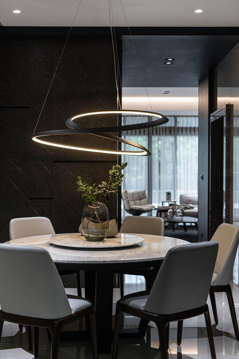 在餐厅天花板悬挂进口餐吊灯,提升餐区的质感氛围,并选用意大利设计品牌的餐吊灯,背后则透过灰黑色仿石纹系统板铺叙壁面,成功包覆卫浴门片,让人忽略入口存在,提升餐厅的质感。
