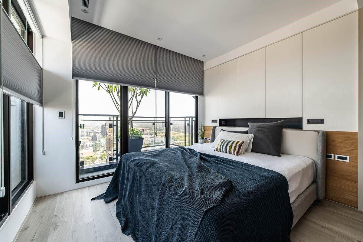 卧室内,援引窗外的日光,以两道立面开窗挹注美好光感,形塑出通透明亮的生活景况。