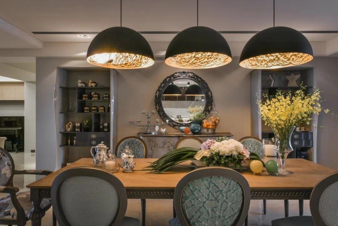 弧形照明的映照下,晕黄的光感让餐厅增添温度,映衬出后方以镜面、矮柜与展示收纳的端景美学。