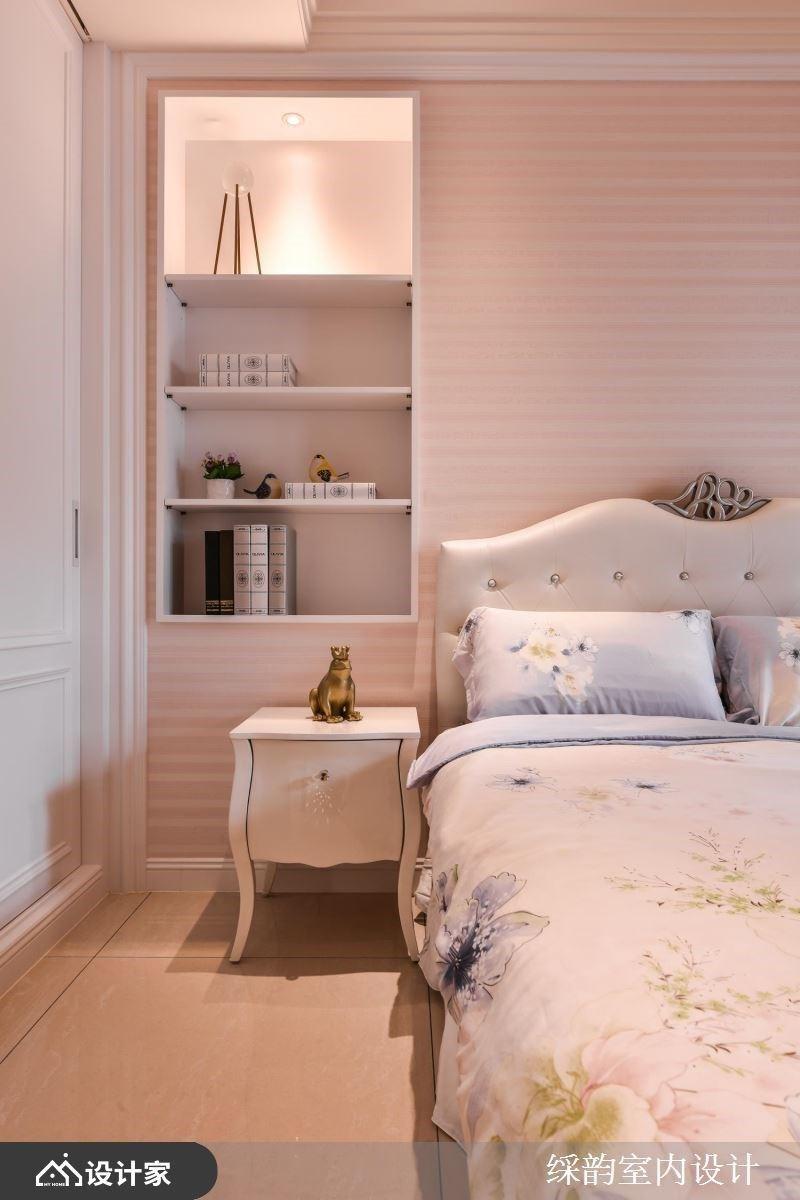 粉色调为主的居室里,床头背墙嵌入开放柜体,陈列书籍与风格小物,下方搭佐一张雅致的古典矮柜,创造柔美的动人端景。